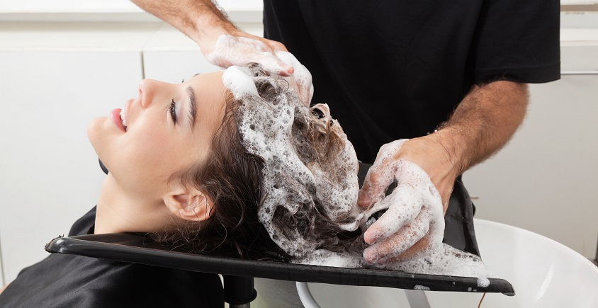 Female client getting hair washed by hairstylist in parlor