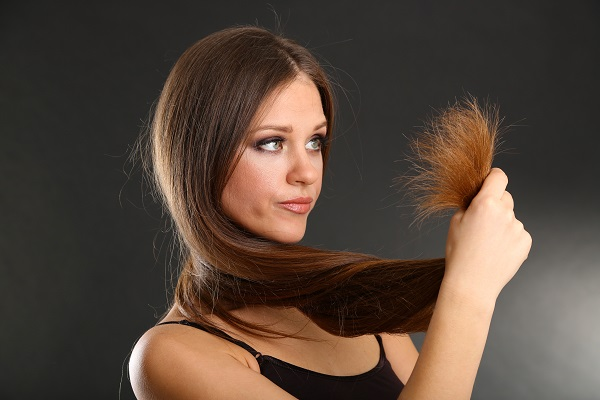 Beautiful woman holding split ends of her long hair,  on black background