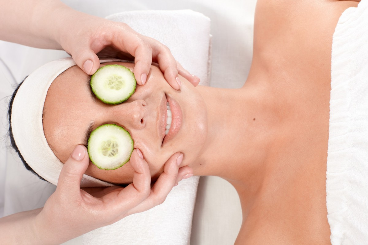 Young woman receiving natural facial treatment with cucumber.