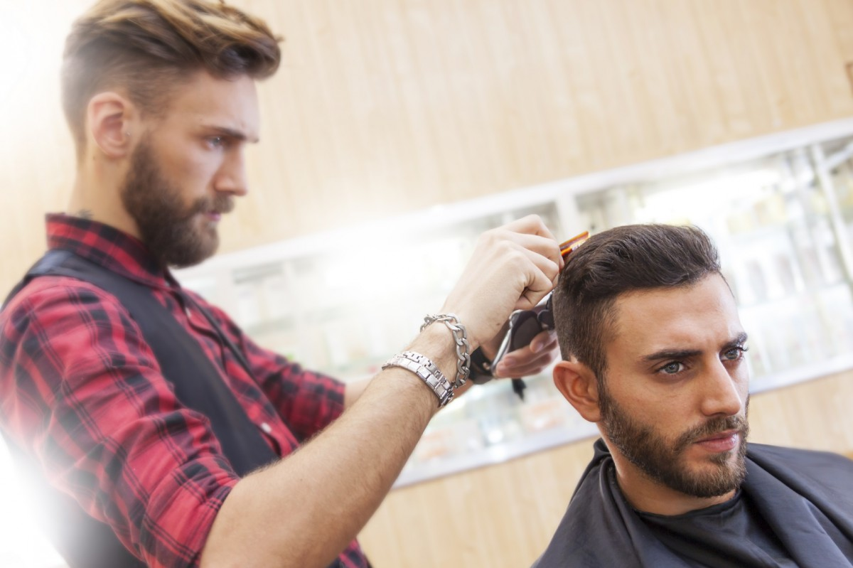 young hipster barber cuts her hair before the pomade