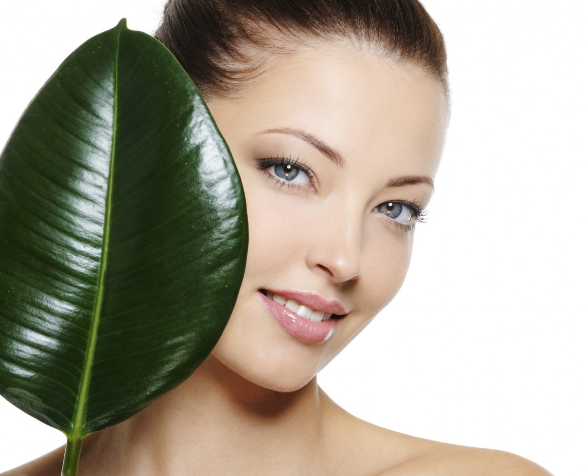 Fresh woman's face with cheerful smile and large green leaf over white backgrouns