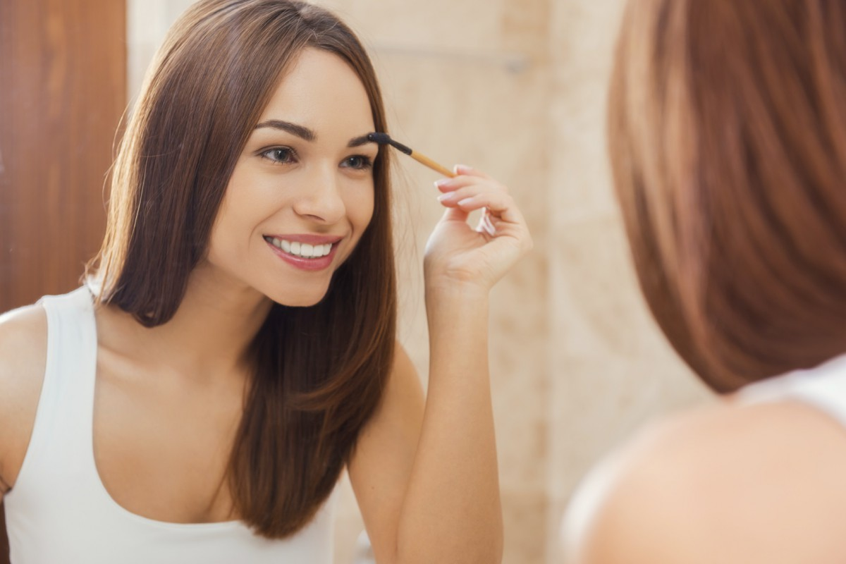 Everything should be perfect. Attractive young woman doing make-up while looking at the mirror and smiling