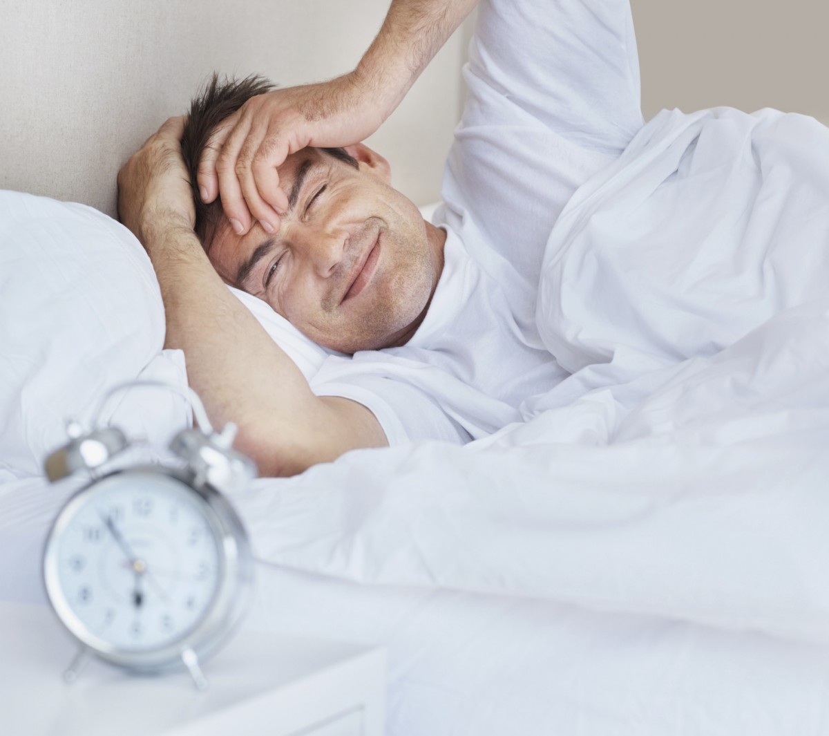 Handsome middle aged man in bed irritated by the ring of the alarm clock