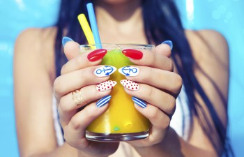 Young woman with marine sailor manicure holding glass of orange juice, summer nail art beauty and drink concept