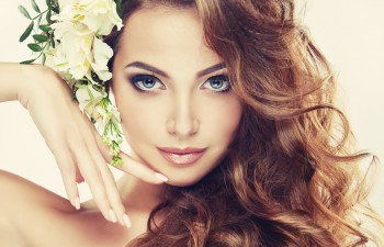 Young gorgeous lady with wavy, dense hair, and charming look.Spring freshness. Girl with delicate pastel flowers in curly hair