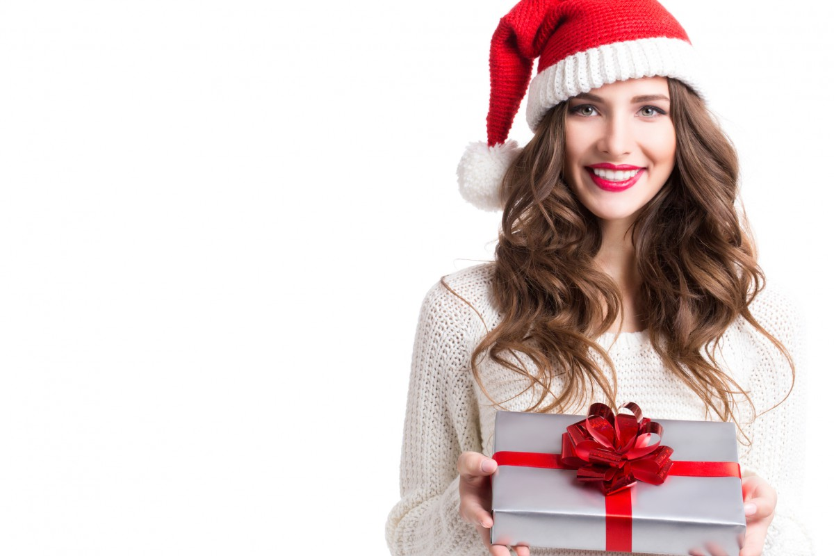 Portrait of a Christmas woman. Cute woman holding a Christmas and New Year gifts. Christmas girl in santa hat with boxes isolated.