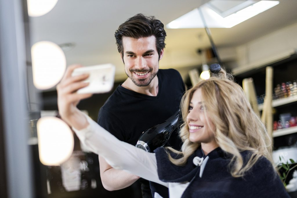 Cosmetologist and client making small talk and selfies