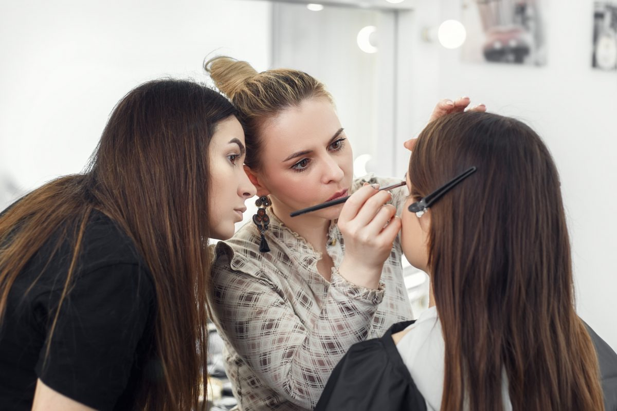 student getting trained on makeup application