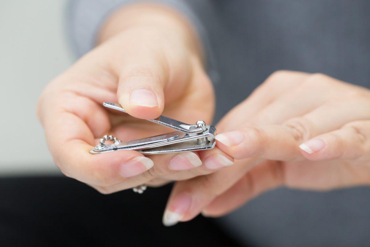 Woman cutting nails using nail clipper