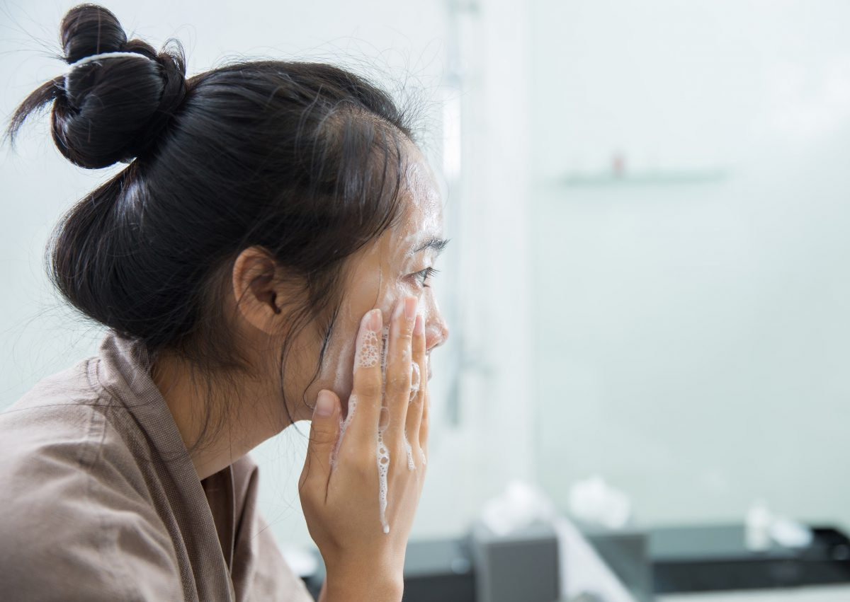 woman washes her face for better skin
