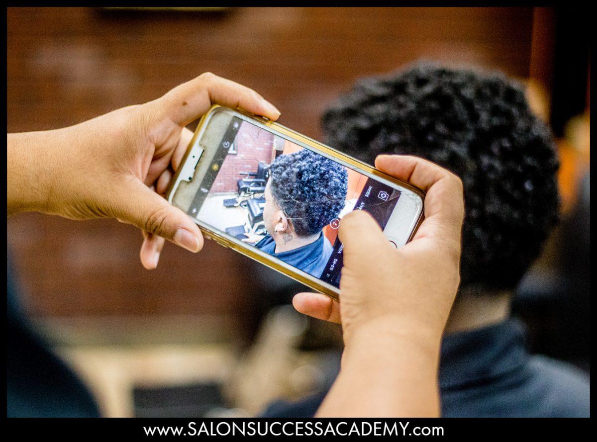 Man helping barber with video portfolio