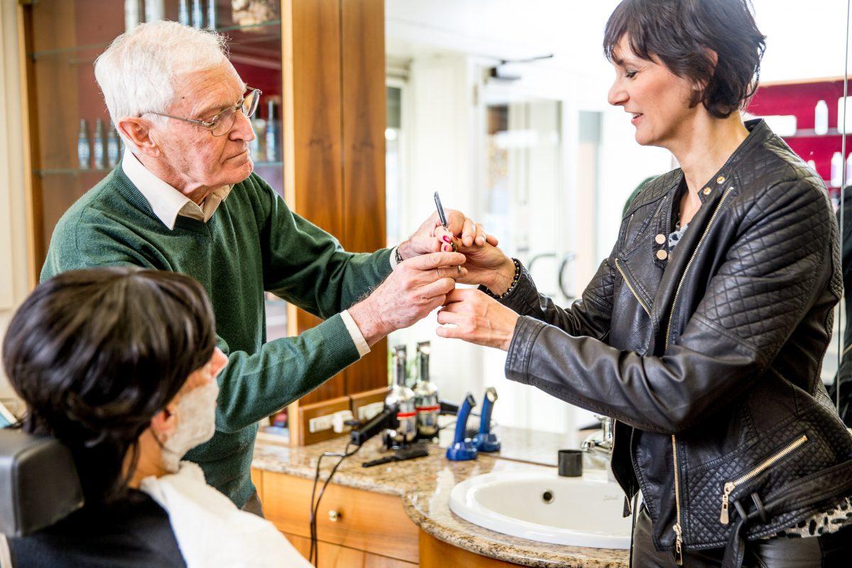 barber teaching a barbering apprentice