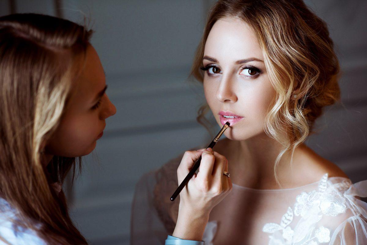 bride putting on bridal makeup