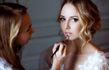 bride putting on bridal makeup