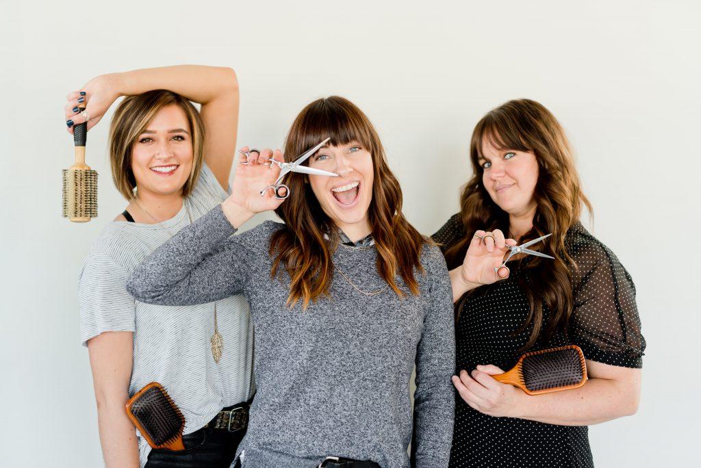 three women holding hair brushes and scissors