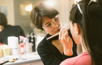 woman applying makeup to another woman's face
