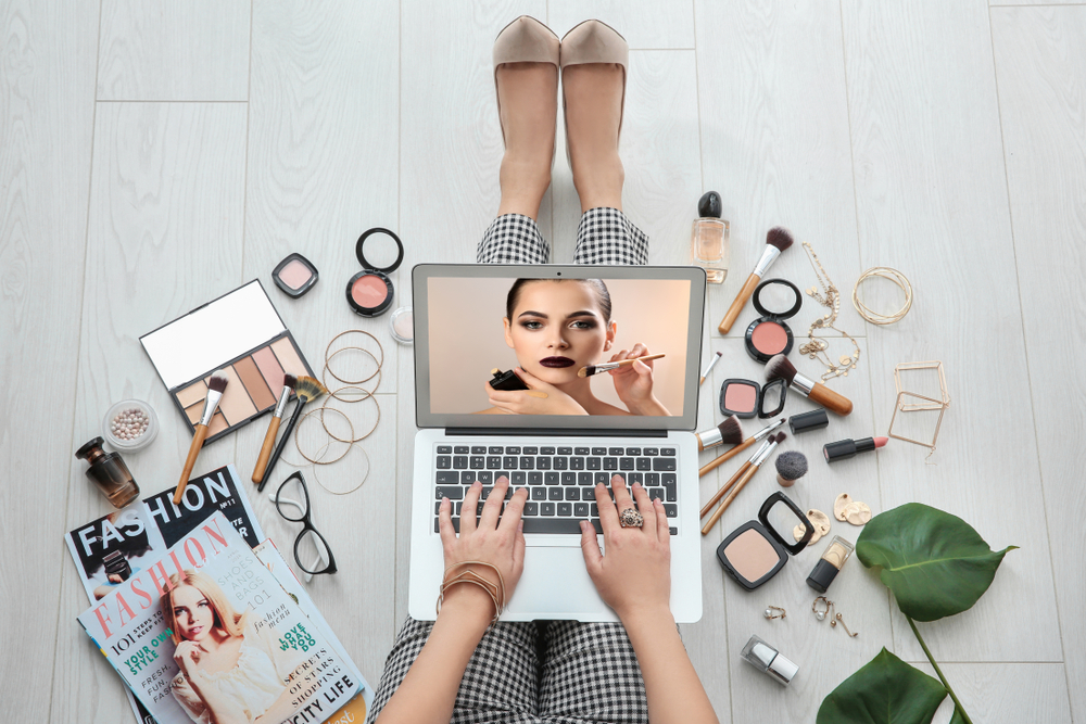 women at a laptop with makeup surrounding her